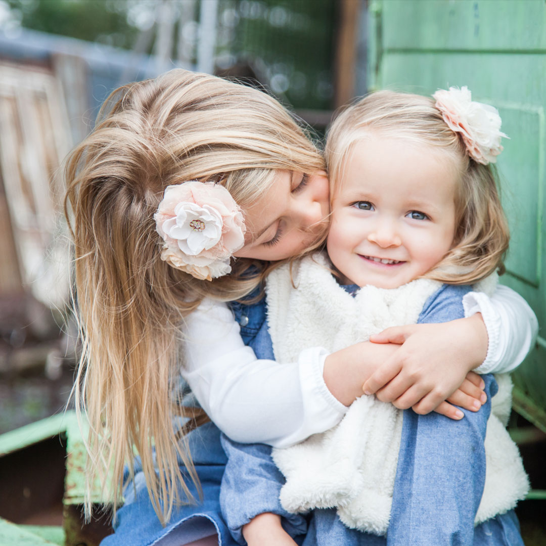 Lifestyle photography, childrens photography, sister kissing little sister on cheek