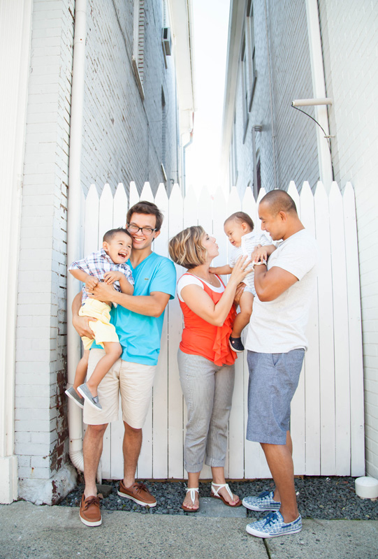 Family Photography and Milestone Photography, vertical shot of family in front of white fence