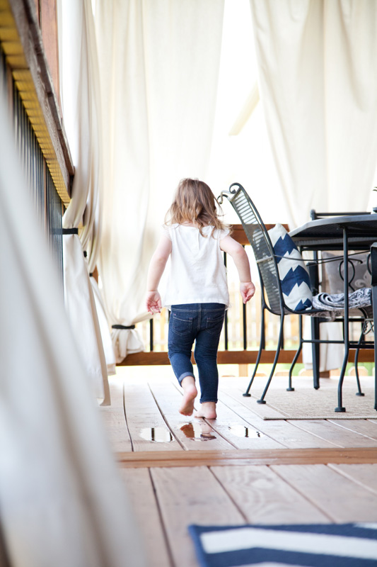 Family Photography and Milestone Photography, little girl tip toeing across porch