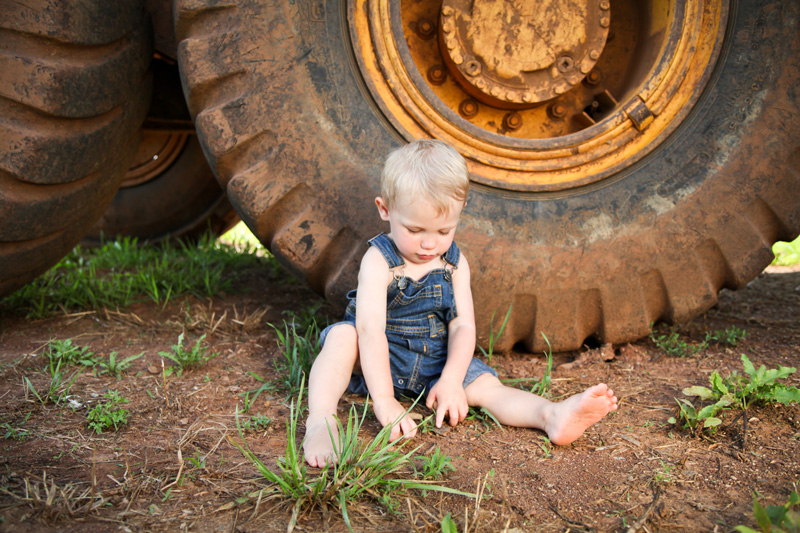 Family Photography and Milestone Photography, little boy sitting in the dirt in front of tractor