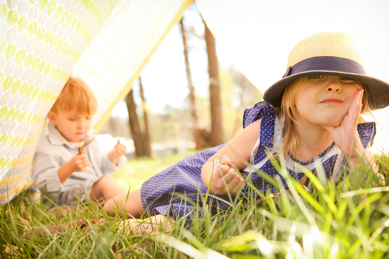 Family Photography and Milestone Photography, brother and sister playing in the grass under a sheet tent
