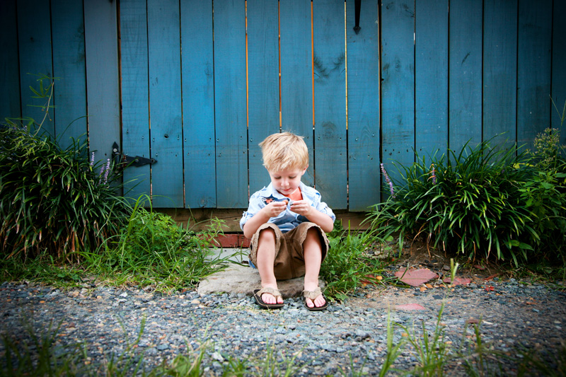 Family Photography and Milestone Photography, little boy sitting in front of blue fence