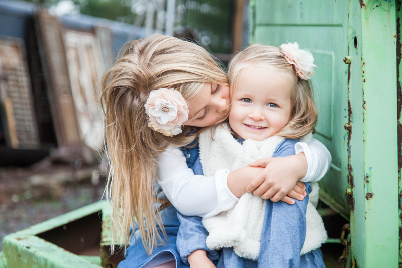Family Photography and Milestone Photography, sister kissing little sister on cheek