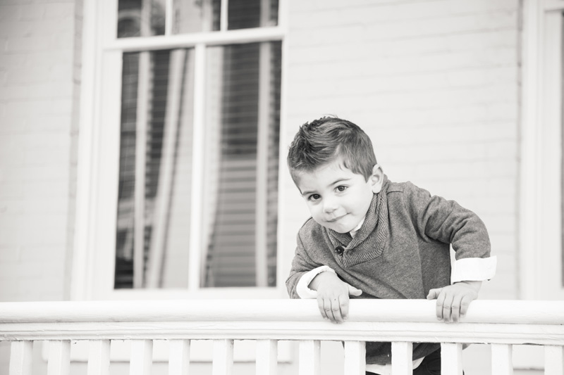 Family Photography and Milestone Photography, black and white of little boy hanging on handrail