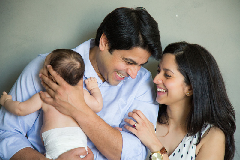 Family Photography and Milestone Photography, couple laughing together with baby in arms
