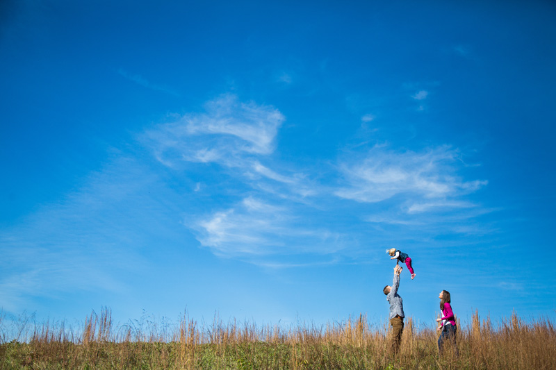 Family Photography and Milestone Photography, wide angle shot of family playing in tall grass