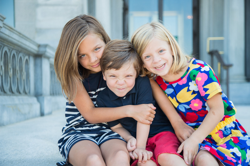 Family Photography and Milestone Photography, two sisters and brother sitting together on steps